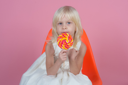 There is no resisting the sugary charms. Little child with sweet lollipop. Happy candy girl. Little girl hold lollipop on stick. Happy childhood food Stock Photo