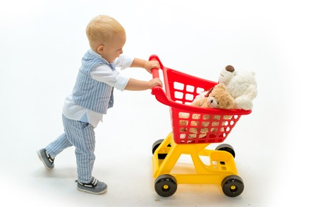 little boy go shopping with full cart. little boy child in toy shop. shopping for children. happy childhood and care. savings on purchases. Excitement. Friendly shop assistant. Needful purchase