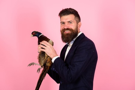 Creative idea. Bird flu. Funny advertising. happy man hold pheasant. Bearded businessman. Hipster. Crazy man on pink. man with poultry meat. Crazy advertising. Unusual idea