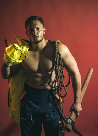 Under construction, coming soon. Hard worker with muscular torso. Muscular man worker. Construction worker or man miner with mining equipment. Mining area under construction Фото со стока