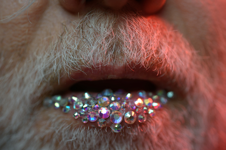 Born with glitter in his veins. Fashion male lip makeup. Man lips with sequins. Exotic transgender man with beard and makeup. Male makeup look
