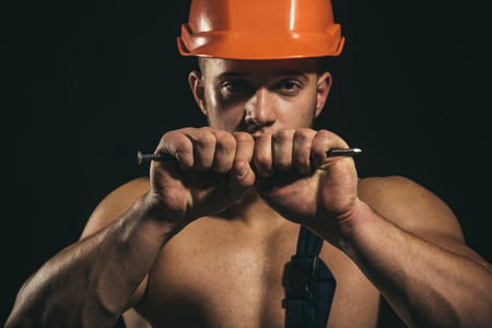 Whatever it takes. Muscular man bend nail. Strong man with muscular arms. Construction worker or builder with biceps triceps. Worker or workman in safety helmet. Proud to be strong