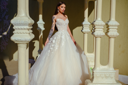 Happy bride before wedding. Beautiful wedding dresses in boutique. Wonderful bridal gown. woman is preparing for wedding. Elegant wedding salon is waiting for bride. Feeling grateful