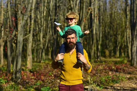 Happy little boy go on journey on fathers shoulder. Journey into the country. The world is yours to explore