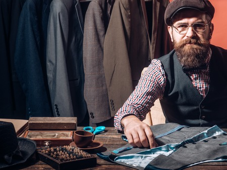 Turning ideas into clothing. His designs are in demand. Bearded man tailor sewing jacket. suit store. business dress code. Handmade. sewing mechanization. retro and modern tailoring workshop Banco de Imagens