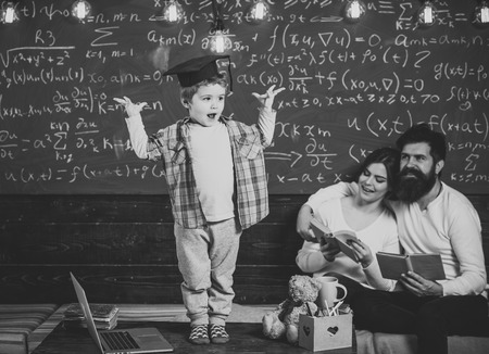 Smart child in graduate cap like to perform. Boy presenting his knowledge to mom and dad. Parents listening their son, checking mistakes with book chalkboard on background. Preparing for exam concept.