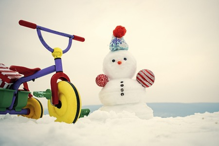 Tricycle and snowman on snowy background