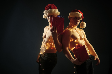 Twins santa with muscular body in garland