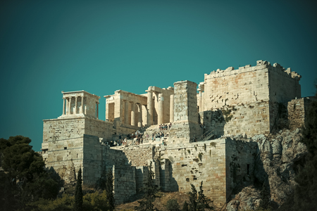 Ruins of ancient acropolis athens surrounded by park or forest. Old building with columns on high platform made out of bricks, sky background. Cultural and architectural heritage concept. Archivio Fotografico - 111295396