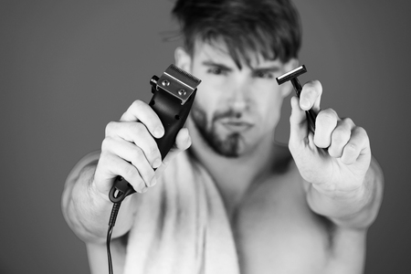Safety razor and electric shaver in hands of handsome man Stock Photo