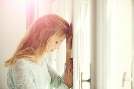 Pretty girl leaned against window frame