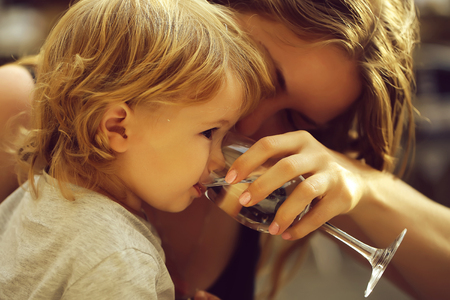 Boy drinking water with mother