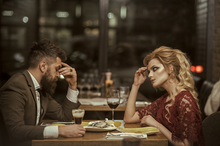 couple with misunderstanding at restaurant. misunderstanding of couple with bearded man and blonde beautiful woman in cafe Stock Photo