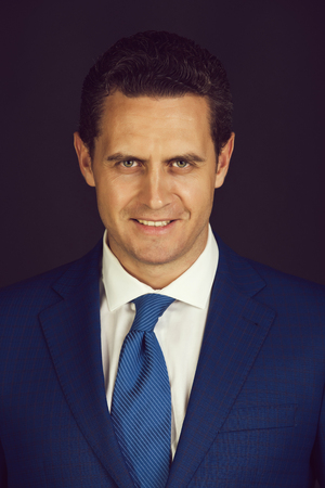 Happy man smiling in fashionable blue suit jacket and tie Фото со стока