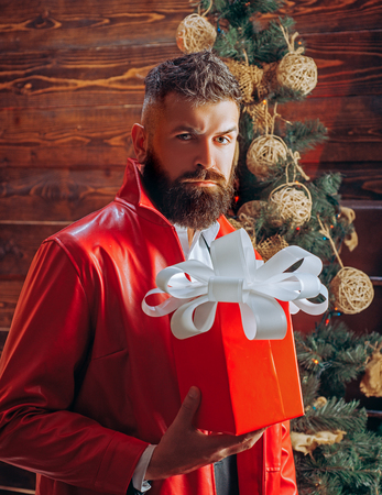 Bearded modern santa wishes Merry christmas and Happy new year. Santa claus in modern red jacket. New year presents in gift box.