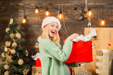 Surprised woman with christmas gift. New year presents in gift box. Happy girl preparing to celebrate new year and merry christmas. Stock Photo
