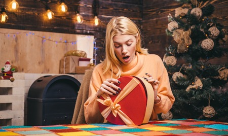 Surprised woman with christmas gift. Happy girl preparing to celebrate new year and merry christmas. New year presents in gift box. Stock Photo