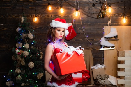 Happy girl preparing to celebrate new year and merry christmas. New year presents in gift box. Holidays, luxury and people concept.