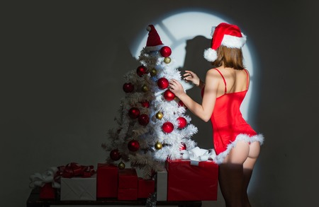 Sexy erotic girl preparing to celebrate new year and merry christmas. Red lingerie for Christmas women. Perfect womans body in sexy lingerie.