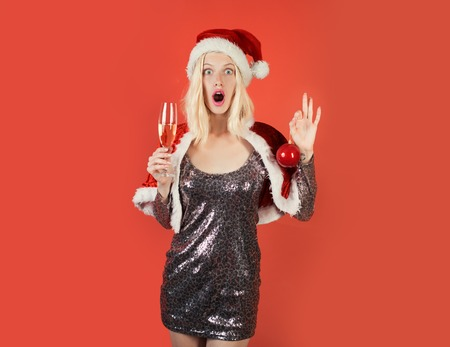 Happy girl preparing to celebrate new year and merry christmas - celebration champagne. Christmas, New Year celebration. Isolated, red background.