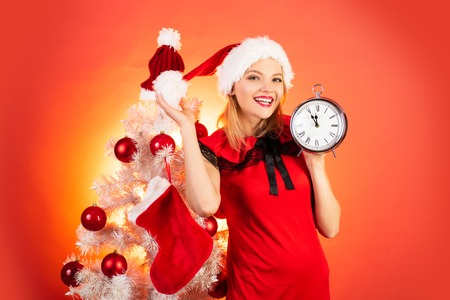 New year clock - time christmas. Happy girl preparing to celebrate new year and merry christmas. Isolated, red background. Stock Photo