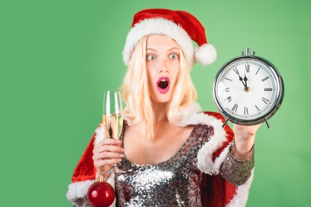 New year clock - time christmas. Surprised woman celebrate new year and merry christmas. Celebration champagne. Isolated, green background.