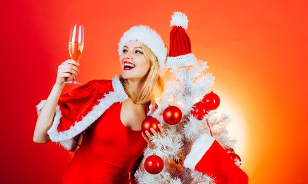 Happy girl preparing to celebrate new year and merry christmas. Celebration champagne. Christmas, New Year celebration. Isolated, red background.
