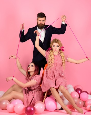 holidays and dolls. dominance and dependence. Creative idea. Love triangle. retro girls and master in party balloons. vintage fashion women puppet and man. Crazy girls and man on pink. Halloween Фото со стока