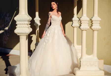 Happy bride before wedding. woman is preparing for wedding. Beautiful wedding dresses in boutique. Elegant wedding salon is waiting for bride. It suits. Wonderful bridal gown. Engagement