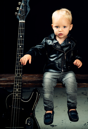 Make some noise. Little rock star. Child boy with guitar. Little guitarist in rocker jacket. Rock style child. Rock and roll music performer. Adorable small music fan. Small musician Stockfoto
