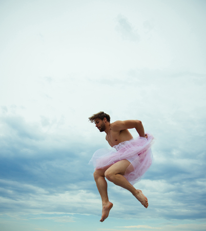 Man dancing in tutu in ballet studio. Crazy ballerina. drag queen. Man in ballerina skirt outdoor. Funny man freak. Inspiration and dreaming. sense of freedom. Man jump on sky background.