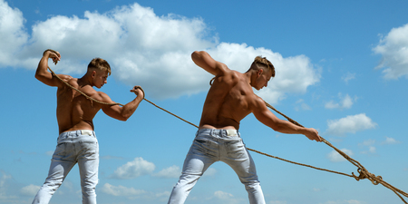 Fighting as a team. Twins men use muscular hand strength. Athletic twins with fit sexy body. Sport exercises for building strength and power. Strong men pull ropes