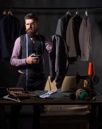 Concentrated on work. Bearded man tailor sewing jacket. business dress code. Handmade. suit store and fashion showroom. sewing mechanization. retro and modern tailoring workshop. Tailor sewing