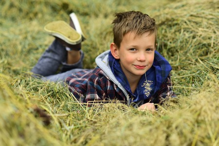 I am a village boy. Little boy in village. Little boy enjoy village life in countryside. Small child lie in hay in farm barn. A wonderful way to relax