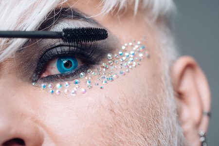 Rethink your lash look. Male makeup artist. Transgender man apply mascara. Male makeup look. Transgender man wear eyeshadows and eyebrow makeup. Fashion male eye makeup