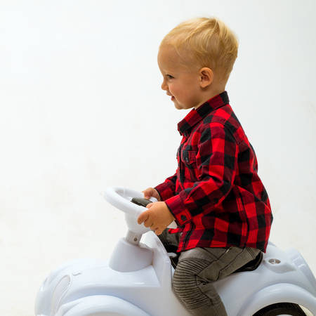 Easy to ride. Little child ride on toy car. Boy child on riding toy. Little baby enjoy playing in kindergarten. Small toddler builds balance and motor skills. Child day care or nursery