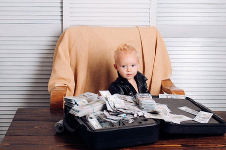 Profitable business. Little entrepreneur work in office. Little boy count money in cash. Boy child with money case. Small child do business accounting in startup company. Startup business costs Stockfoto