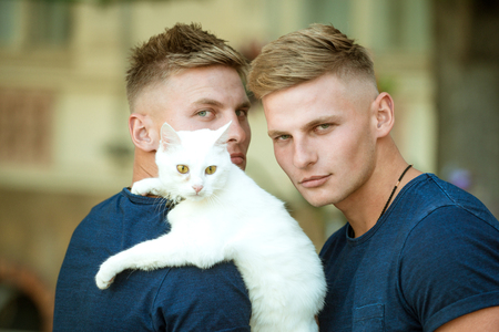 Perfect furry friend. Cat is a part of their family. Muscular men with cute cat. Happy cat owners on walk with pet. Twins men hold pedigree cat. Happy twins with muscular look Stock Photo