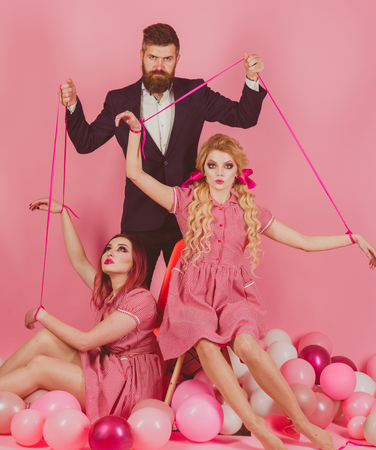 holidays and dolls. dominance and dependence. vintage fashion women puppet and man. Creative idea. Love triangle. retro girls and master in party balloons. Crazy girls and man on pink. Halloween Stock Photo