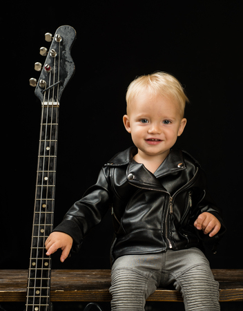 Live life loud. Little guitarist in rocker jacket. Rock style child. Rock and roll music performer. Stockfoto