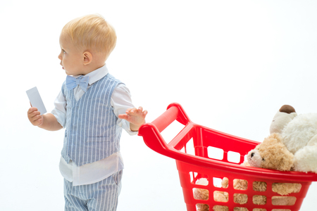 little boy child in toy shop with credit card. savings on purchases. little boy go shopping with full cart. shopping for children. happy childhood and care. Time to shop. Pleasant price. Hard choice Reklamní fotografie