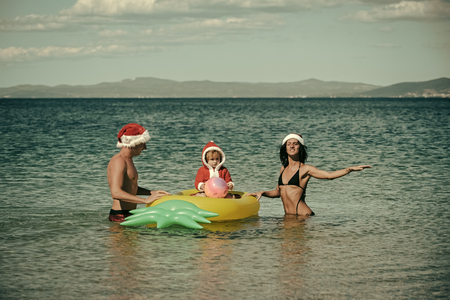 Christmas happy family on pineapple mattress in water.