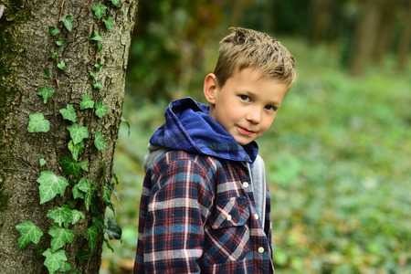 Every single childhood matters. Small boy enjoy childhood years. Small boy play in forest. Childhood is a short season