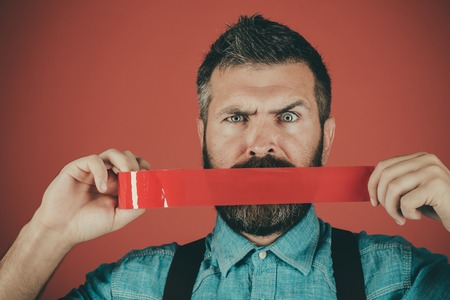 man wrapping mouth by adhesive tape. censorship. Brutal bearded male. Mind control and propaganda. International Human Right day. Concept freedom of speech and press. Fight against lies and falsity