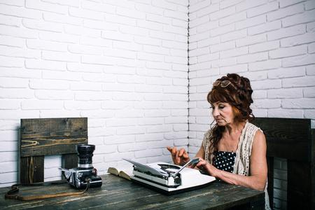 Work for seniors. Old woman work in writer office. Senior woman type on retro typewriter. Journalist work in vintage office. Senior writer at desk. Female reporter or journalist writing on typewriter