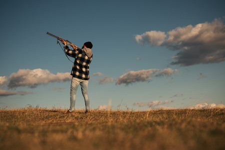 Process of duck hunting. Hunter in the fall hunting season. Hunter with shotgun gun on hunt. Skeet shooting.