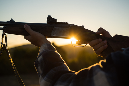 Rifle Hunter Silhouetted in Beautiful Sunset. Cartridges shotgun. Pulled the trigger of the shotgun.