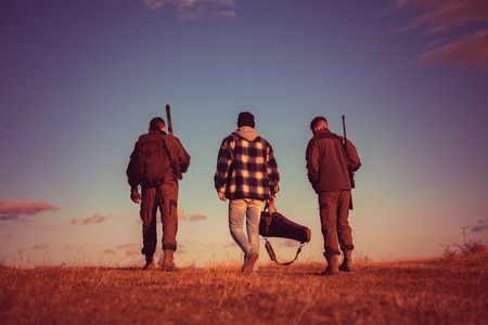 Hunters after the hunt. Rifle Hunters Silhouetted in Beautiful Sunset. Closed and open hunting season. Hunting Licenses.