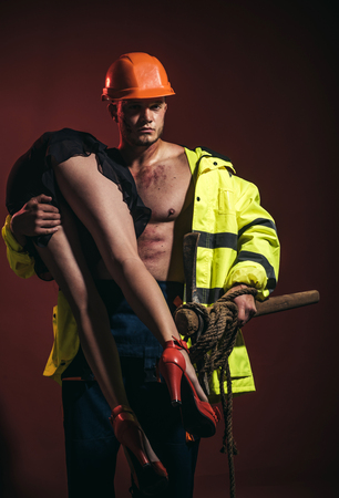 Passionate couple concept. Vibrant with passion. Sexual game is your passion. Firefighter sexy body muscle man holding saved girl. Hot and sexy. Фото со стока