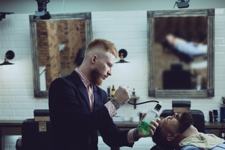 Razor blade. Bearded man getting haircut by hairdresser and sitting in chair at barbershop. Styling with the shaver. Men after shave. Aftershave cosmetic product. Guys face skin.